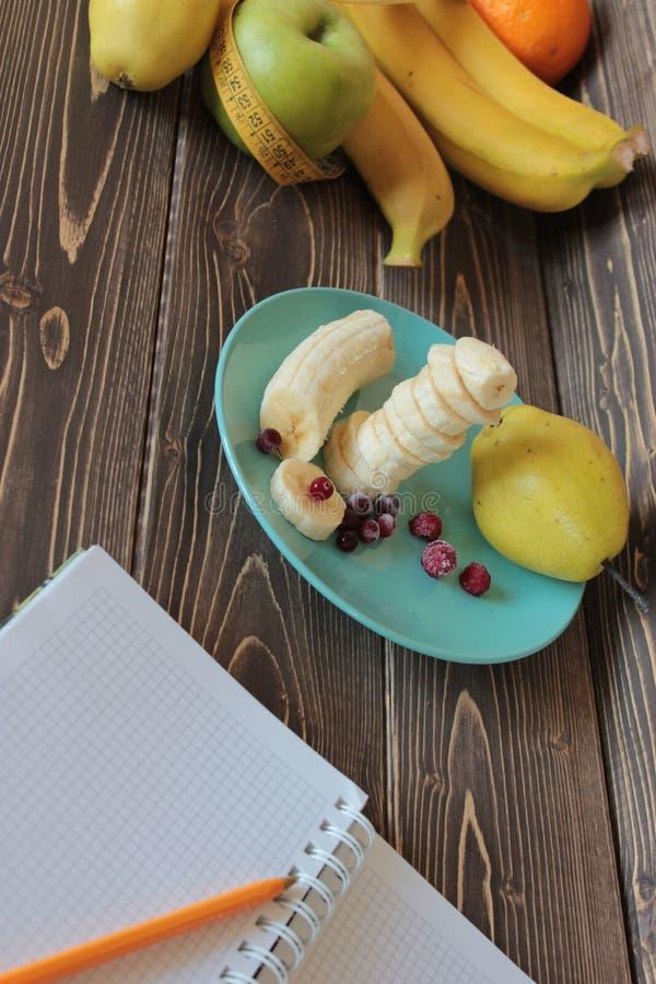 Plátanos, corte en un plato con el arándano congelado y cuaderno fotografía de archivo