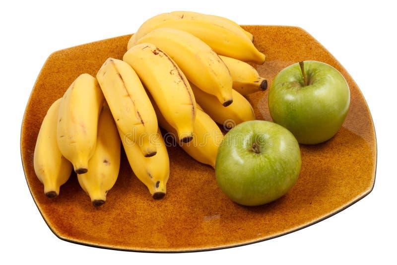 Plátanos y manzanas en el plato imagen de archivo