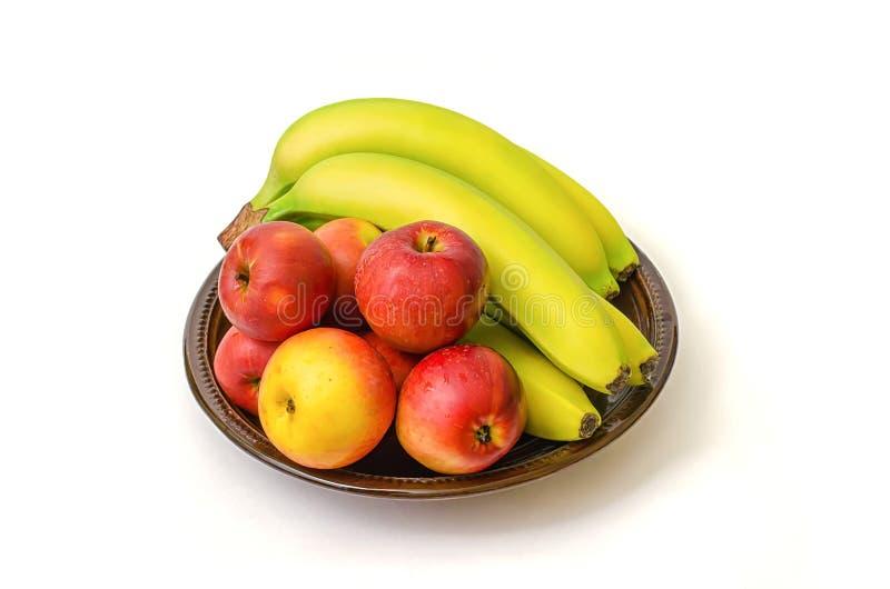 Plátanos y manzanas en el plato en el fondo blanco imagenes de archivo