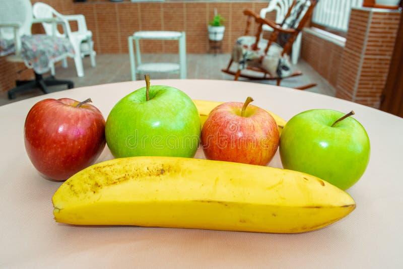 Plátanos y manzanas en fila en el jardín foto de archivo