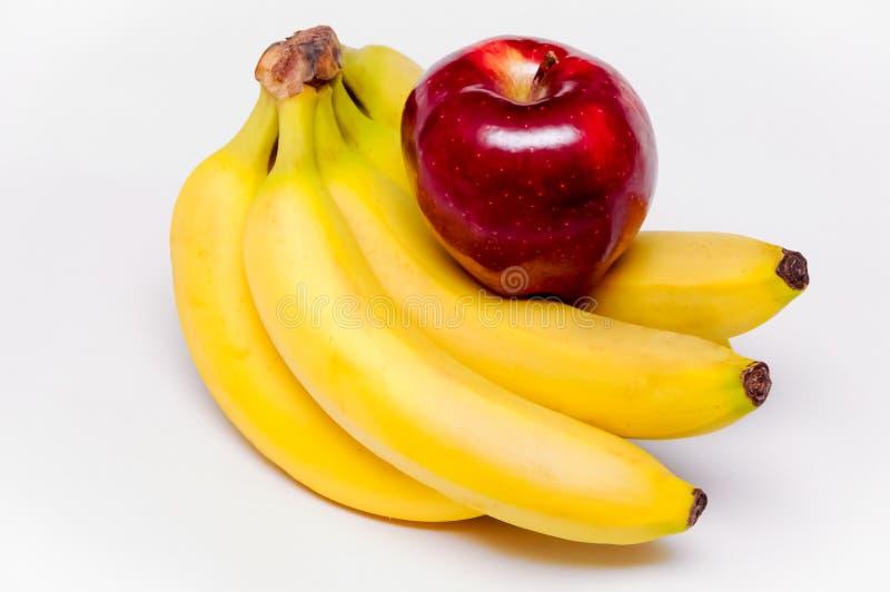 Plátanos y una manzana imagen de archivo libre de regalías