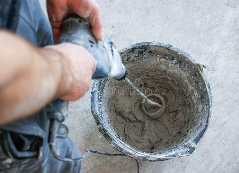 Plâtre de mélange de travailleur avec un foret dans un seau photographie stock libre de droits