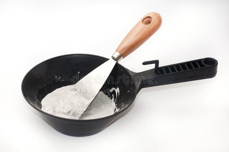 Plâtre et eau dans une cuvette noire avec une spatule pour le mélange image stock