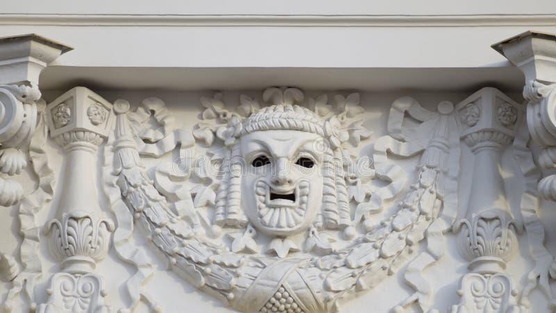 Plâtrez le masque sur le mur du théâtre images stock