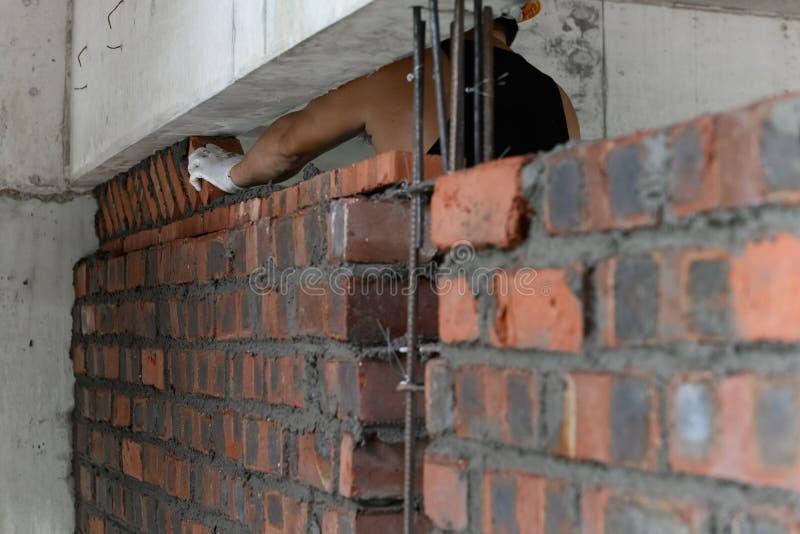 Plâtrier composant le mur de briques avec le ciment photos libres de droits