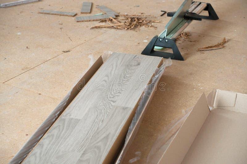 Plätera giljotin och skivor av laminaten som är klara för installation royaltyfri fotografi