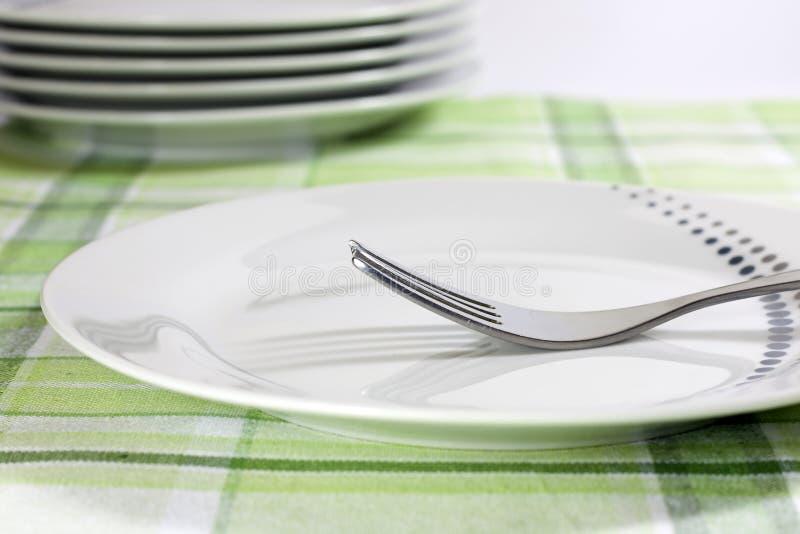 Pläterar på tablecloth i kök arkivbild