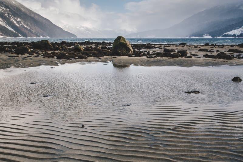 Plätschernde Sand-Muster auf Alaska-Strand mit entfernten Wellen auf Rocky Shore lizenzfreies stockfoto