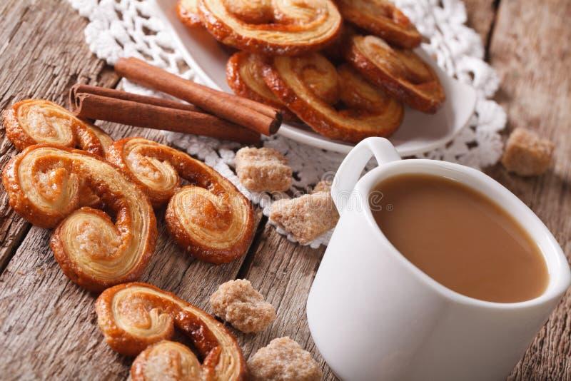 Plätzchen des Blätterteiges Palmiers und des Kaffees mit Milchnahaufnahme, h stockbilder
