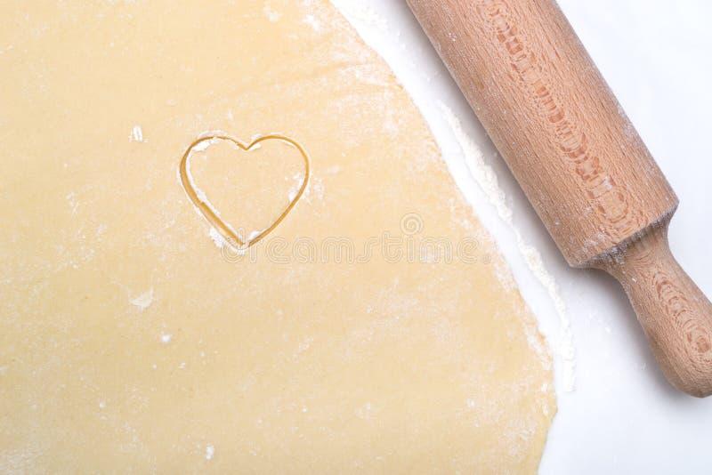 Plätzchen in Form eines Herzens schnitten vom Teig heraus stockfotografie