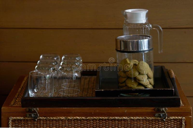 Plätzchen im Glasgefäß im hölzernen Behälter mit Gläsern und Flasche für Se stockbilder
