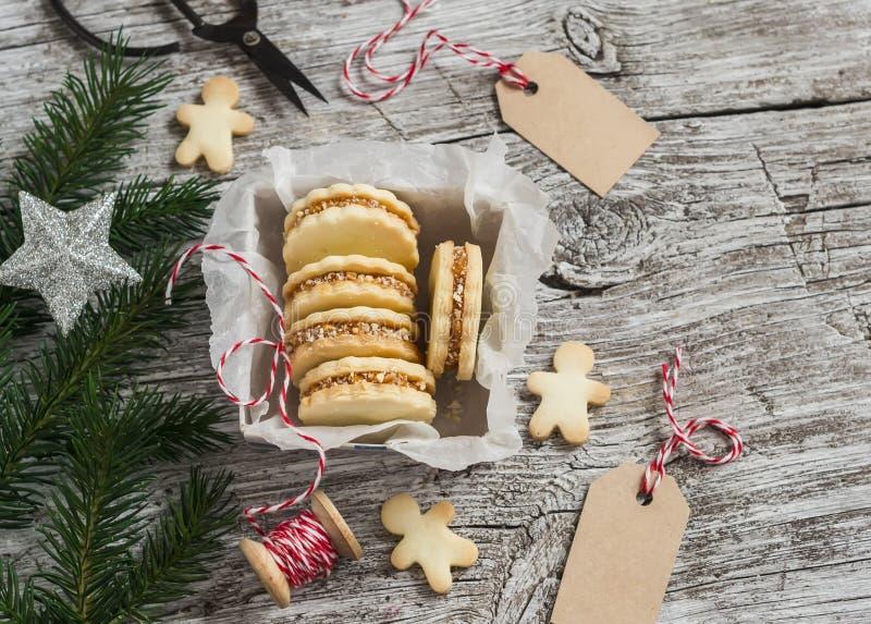 Plätzchen mit Karamellcreme und -walnüssen in einem Weinlesemetallkasten, Weihnachtsdekoration und ein sauberes, Empty tag stockfotografie