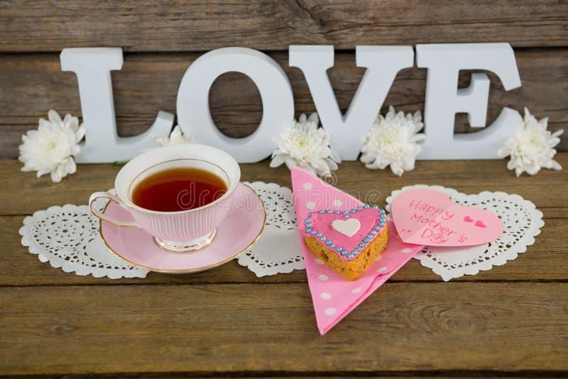 Plätzchen, Tee, Blumen und glückliche Muttertageskarte mit Liebe simsen lizenzfreie stockbilder
