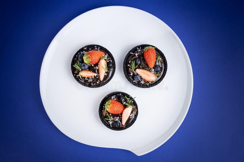 Plätzchenkrusten-Schokoladentörtchen mit Blaubeer- und Erdbeersatz auf blauem Hintergrund lizenzfreie stockfotos