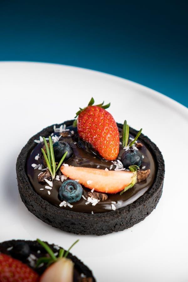 Plätzchenkrusten-Schokoladentörtchen mit Blaubeer- und Erdbeersatz auf blauem Hintergrund lizenzfreies stockbild
