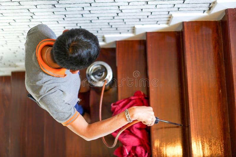 Plågan/termit kontrollerar service på trätrappan i det nya huset som har termittecken inom den arkivfoton