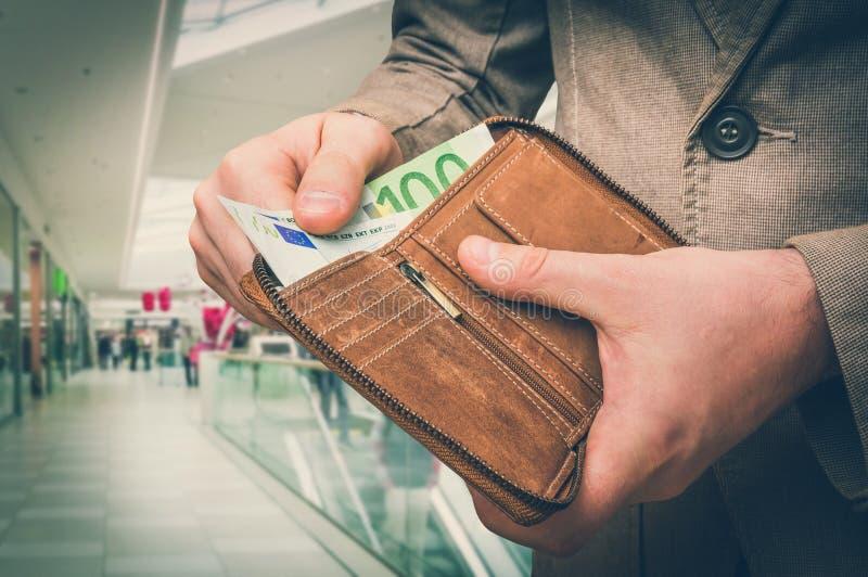 Plånbok med europengar i manhänder i shoppingmitt arkivfoton