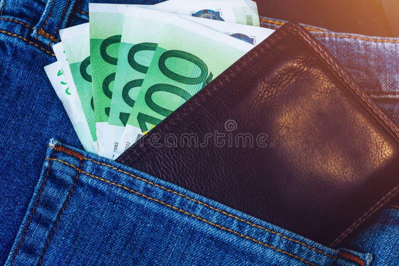 Plånbok med eurosedlar Den CaBrown plånboken med europengar i jeansen stoppa i fickan Plånbok med eurosedlar Kassa in royaltyfri foto