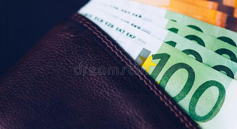 Plånbok med eurosedlar Kassa in plånboken på en svart bakgrund Europengar piskar in plånboken arkivbilder