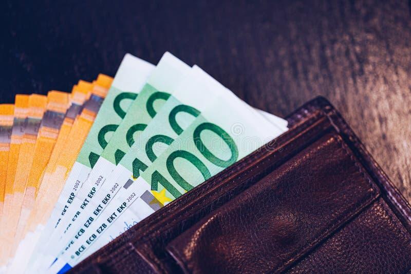 Plånbok med eurosedlar Kassa in plånboken på en svart bakgrund Europengar piskar in plånboken arkivbild