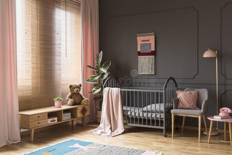 Plüschspielzeug auf hölzernem Schrank nahe bei grauer Wiege in Kind-` s vorüber stockbild