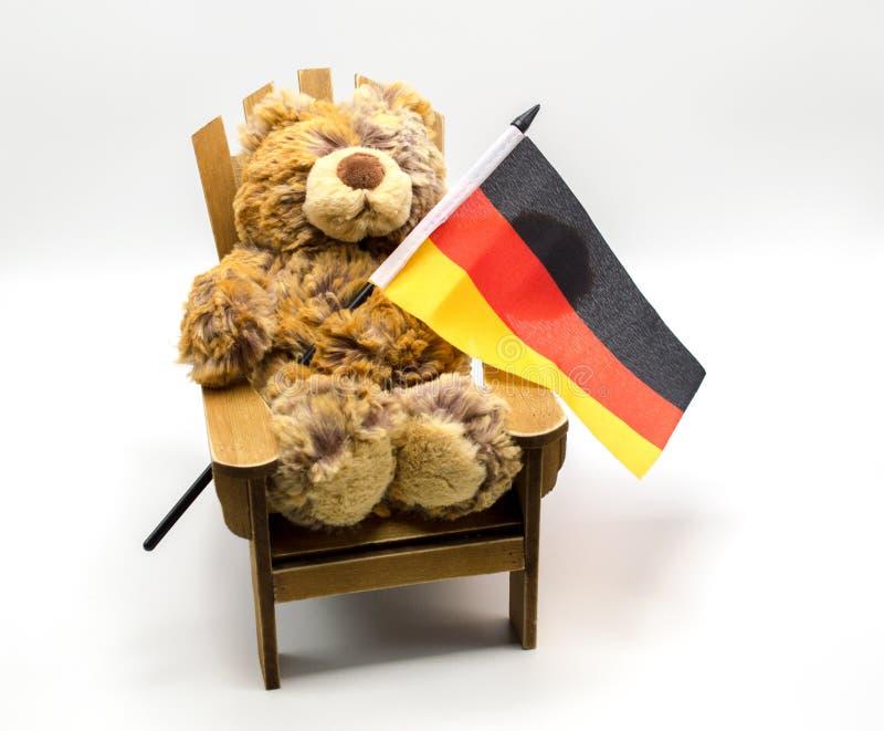 Plüschspielzeugbär in einem Stuhl, der eine dreifarbige deutsche Flagge lokalisiert auf Weiß hält lizenzfreie stockfotos