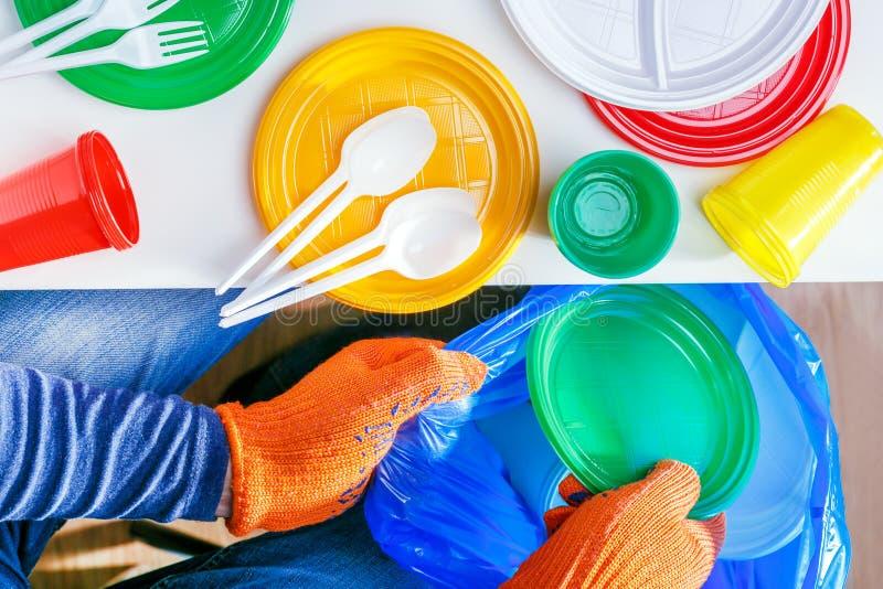 Pl?stico do uso da proibi??o ?nico O homem joga para fora pratos plásticos em um saco de plástico imagens de stock royalty free