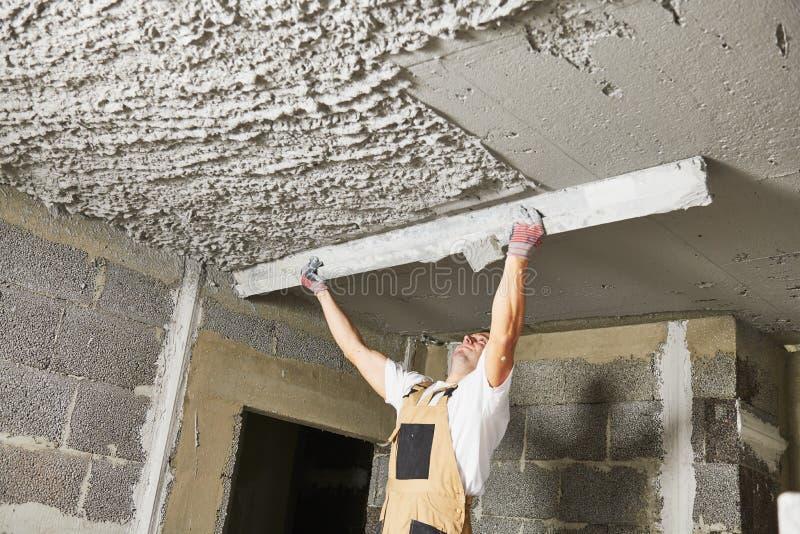 Pl?trier lissant le mortier de pl?tre sur le plafond avec le screeder photo libre de droits