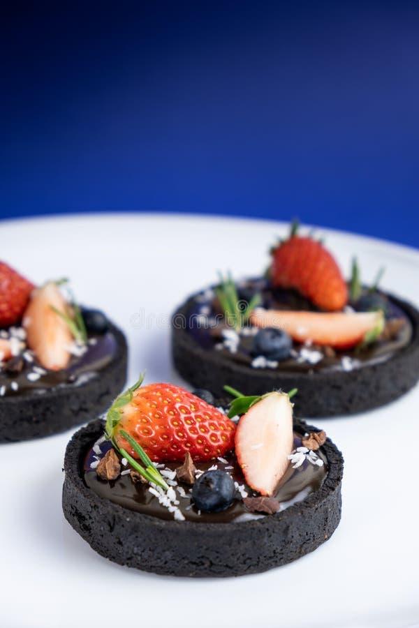 Pl?tzchenkrusten-Schokoladent?rtchen mit Blaubeer- und Erdbeersatz auf blauem Hintergrund stockfotos
