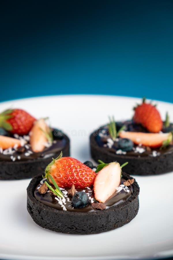Pl?tzchenkrusten-Schokoladent?rtchen mit Blaubeer- und Erdbeersatz auf blauem Hintergrund stockfotografie
