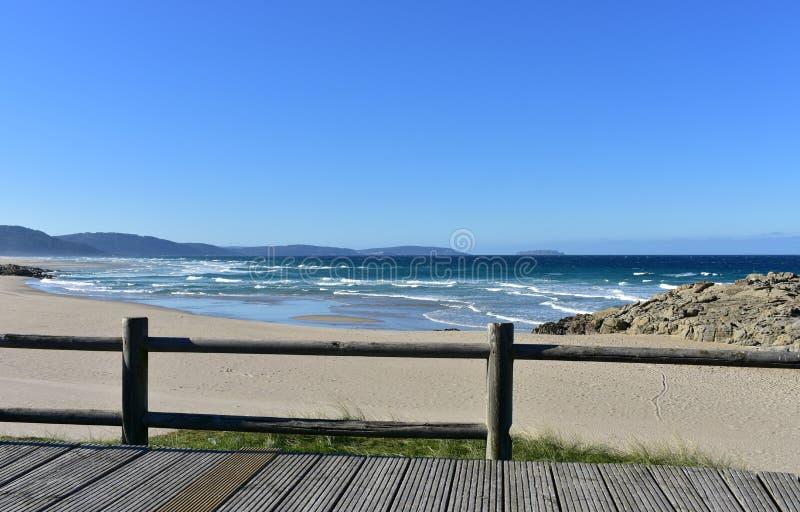 Plaża z drewnianym boardwalk i ogrodzeniem Złoty piasek, skały, dziki morze z falami i biel, pienimy się Niebieskie niebo, słonec zdjęcia stock