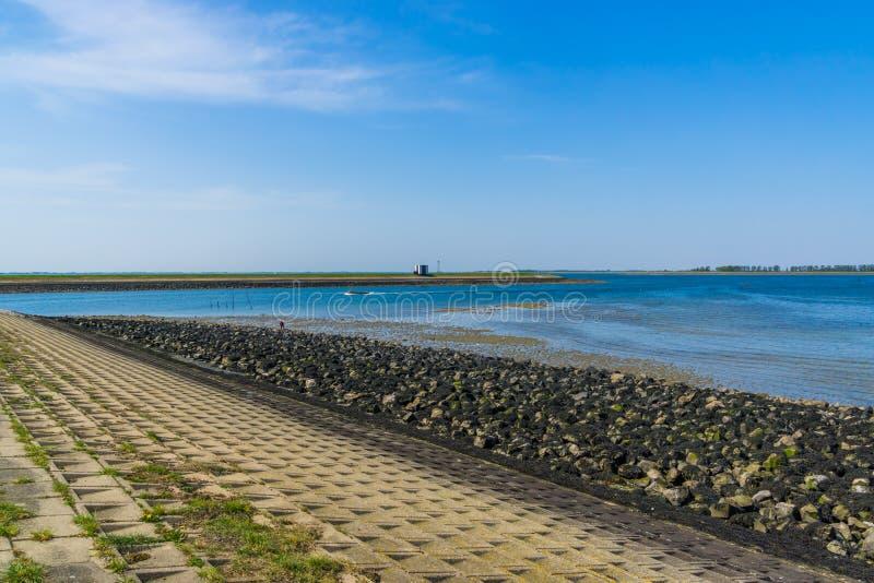 Plaża tholen z niebieskim niebem dennymi skałami i, Bergse diepsluis, oosterschelde, oesterdam, Zeeland holandie fotografia royalty free