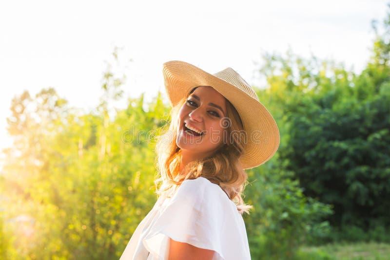 Plażowa kobieta śmia się mieć zabawę w wakacji wakacjach Dziewczyna jest ubranym dużego słomianego kapelusz fotografia royalty free