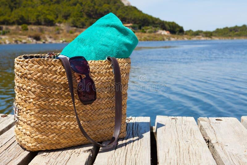 Plażowa torba z ręcznikiem przy jeziorem zdjęcie royalty free