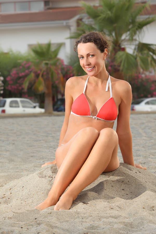 plażowego bikini obsiadania uśmiechnięta kobieta obrazy stock