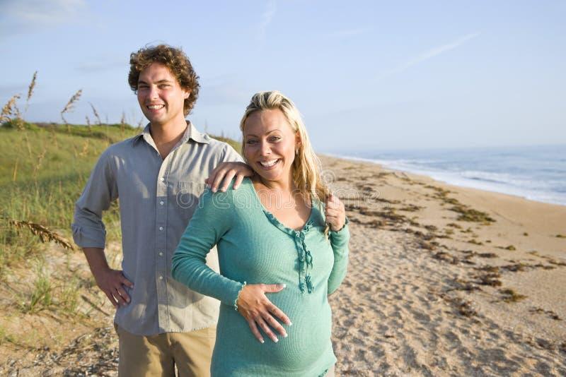 plażowej pary szczęśliwi ciężarni trwanie potomstwa zdjęcia stock