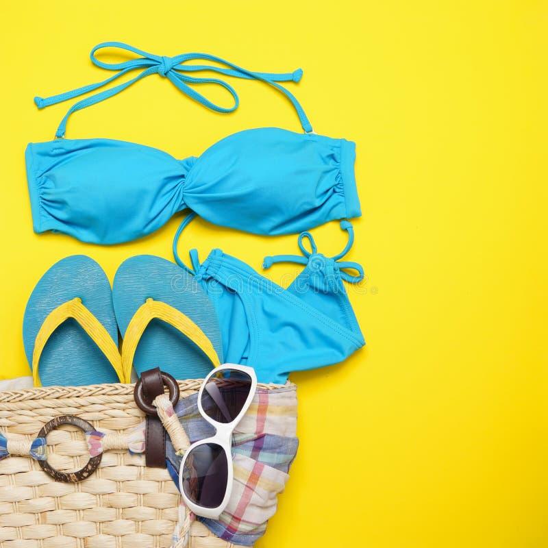 Plażowi akcesoria okulary przeciwsłoneczni, bikini, klapy i pasiasty kapelusz na żółtym tle -, Lato jest nadchodzącym pojęciem obraz stock