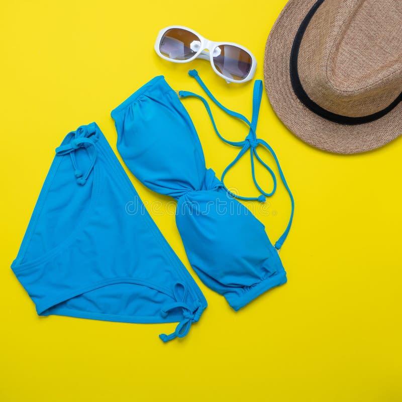 Plażowi akcesoria okulary przeciwsłoneczni, bikini, klapy i pasiasty kapelusz na żółtym tle -, Lato jest nadchodzącym pojęciem fotografia stock