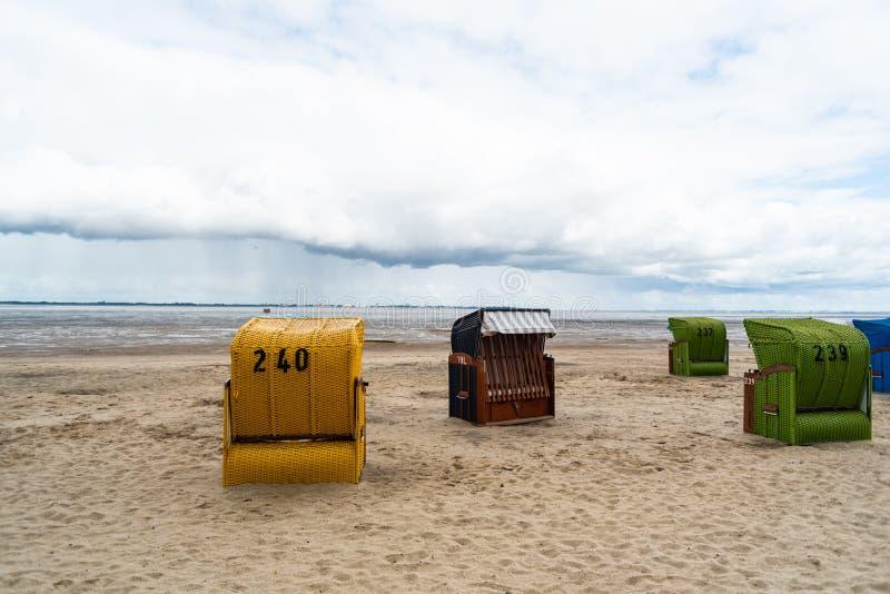 Plażowi krzesła inaczej reżyserujący przy plażą w Dangast Niemcy obrazy stock