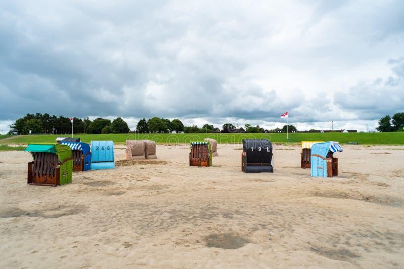 Plażowi krzesła inaczej reżyserujący przy plażą w Dangast Niemcy zdjęcia stock