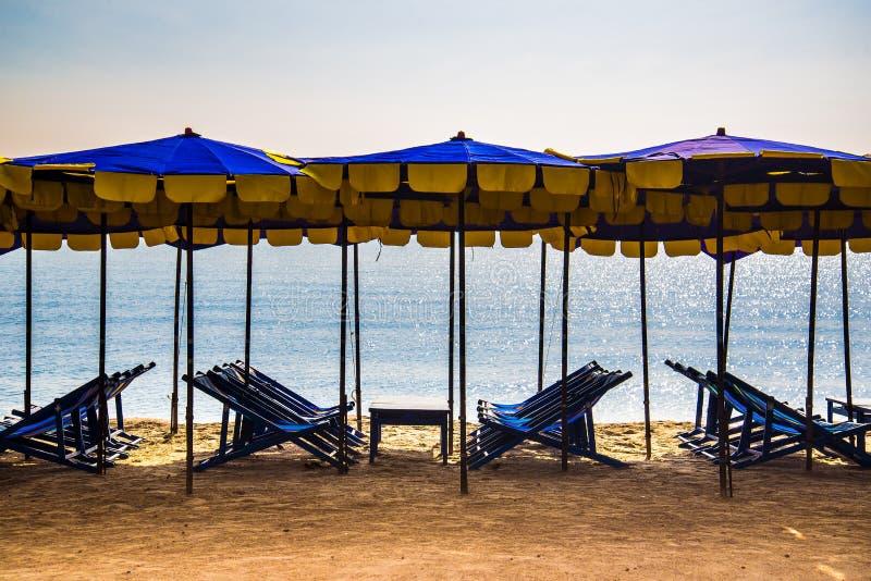 Plażowi krzesła na piasku gruntują z parasolami w lato sezonie obrazy royalty free