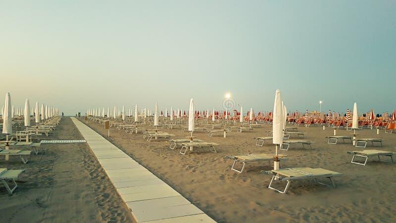 Plażowi krzesła z parasolem zamykali w wieczór w Rimini, Ital obrazy royalty free