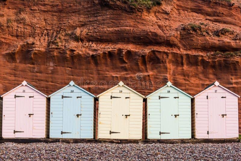 Plażowy buda rząd w pastelowych kolorach, czerwieni rockowy tło fotografia stock