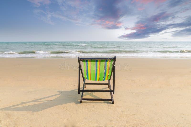 Plażowy krzesło na białej piasek plaży z zmierzchu mrocznym niebem i kopii przestrzenią Lata tło Lata krajobrazowy pojęcie romant obraz stock