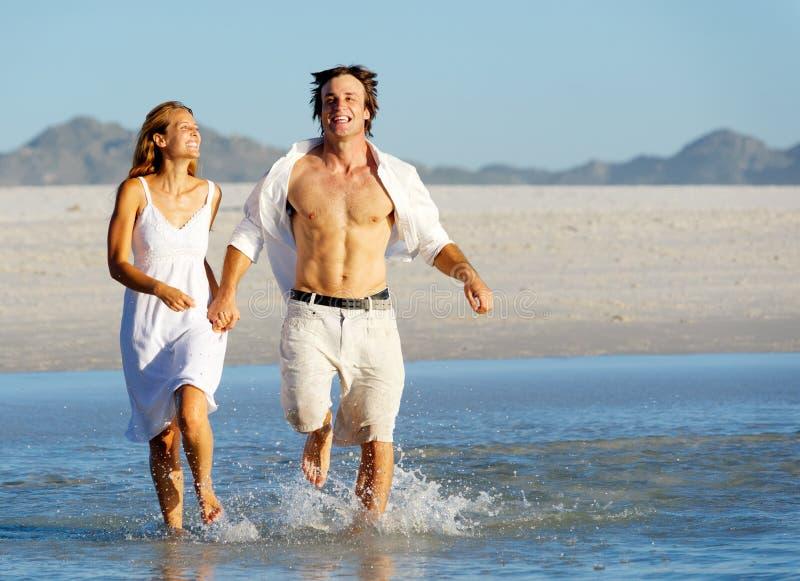 plażowy pary bieg pluśnięcie obrazy royalty free