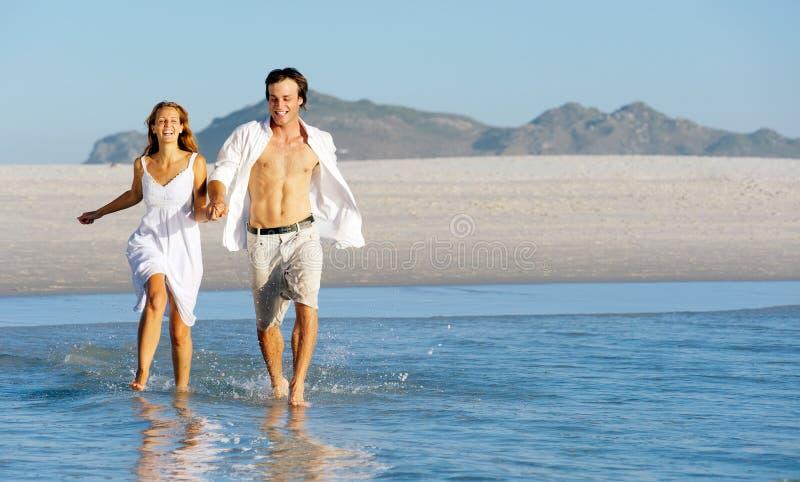 plażowy pary bieg pluśnięcie zdjęcie stock