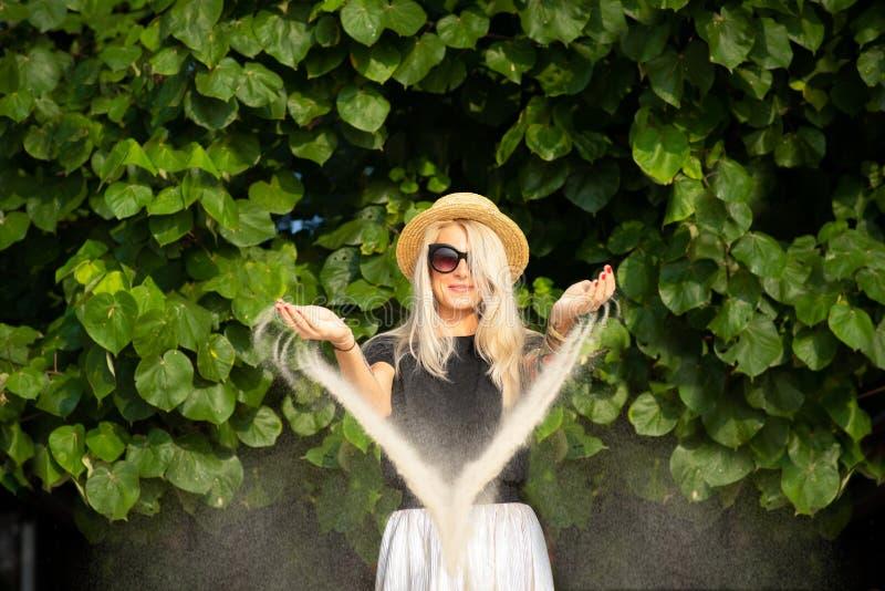 Plażowy piasek budzi się od ręk piękna blondynka w okularach przeciwsłonecznych Wyrzuca? na brzeg wakacje Portret nowo?ytna dziew obrazy stock
