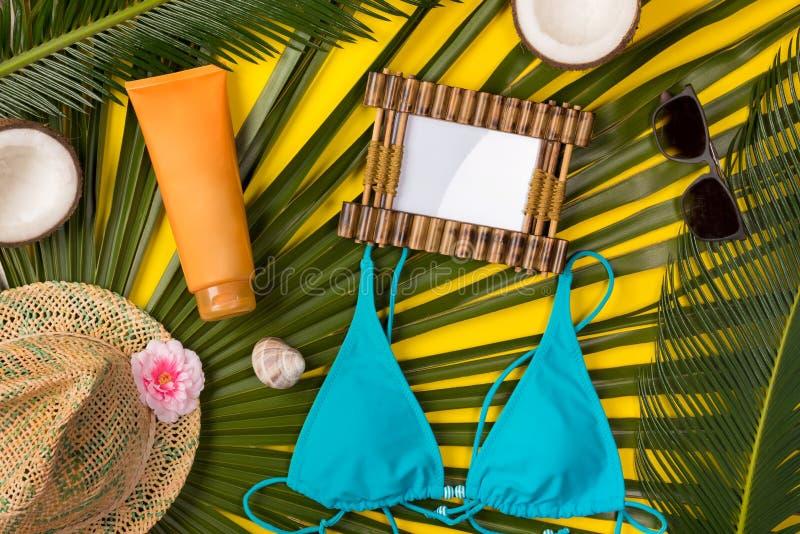 Plażowy temat na żółtym tle Plażowi akcesoria, palma opuszczają na żółtym tle, fotografii rama fotografia stock