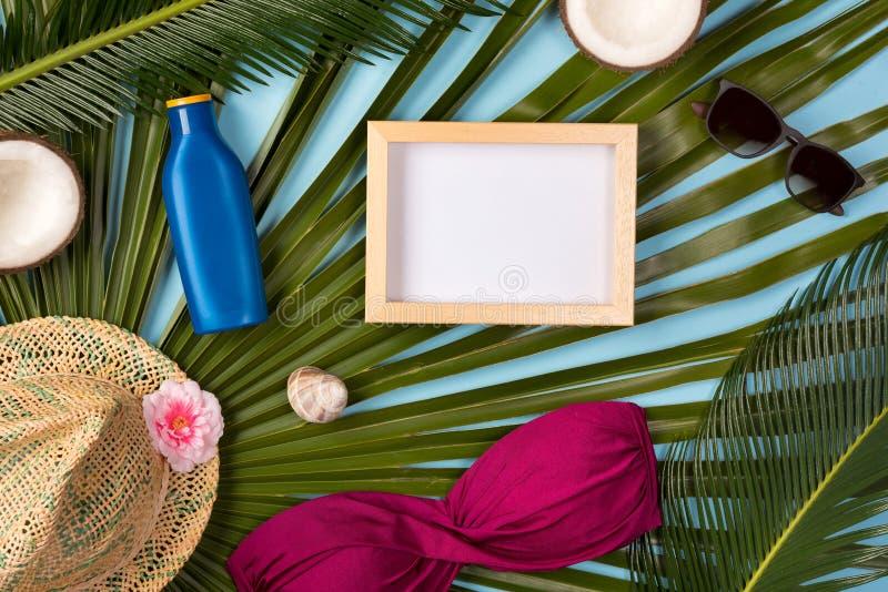 Plażowy temat na błękitnym tle Plażowi akcesoria, palma opuszczają na błękitnym tle, fotografii rama obraz stock