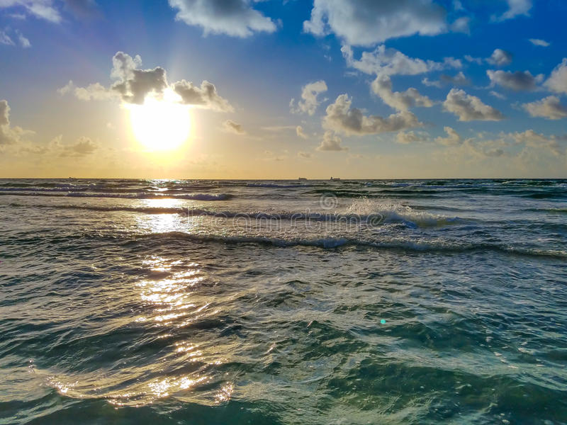 Plażowy wschód słońca, ocean fala, chmury i niebieskie niebo, zdjęcia royalty free